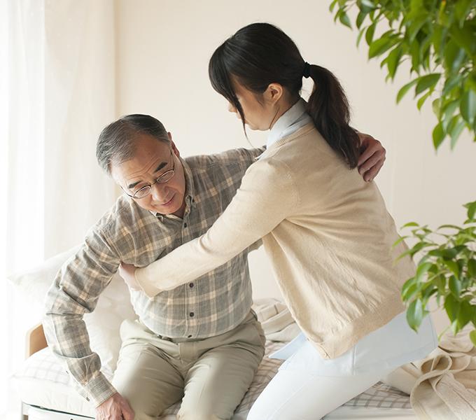 立ち上がる介助を受けている高齢男性